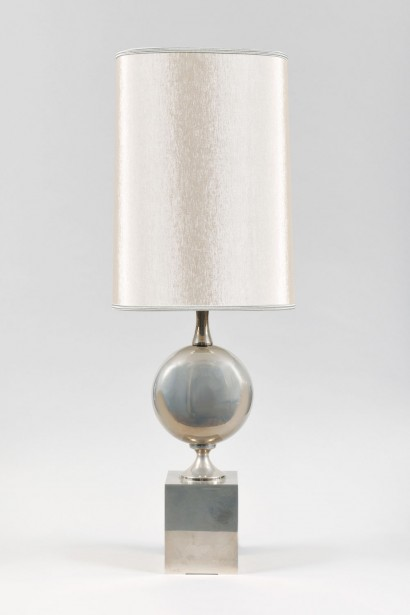 Elégante lampe à poser      Maison Barbier, Paris  Circa 1970     Acier inoxydable  Abat-jour sur mesure en soie ivoire gansée  Hauteur totale avec abat-jour: 71 cm, Hauteur jusqu'à la douille: 37 cm  L. 14 cm, P. 10 cm