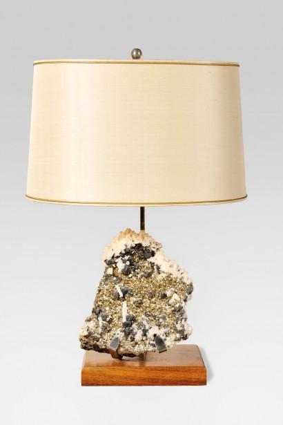 Lampe à poser     Circa 1960-1970  Dans le goût de Willy Daro     Pyrite montée en base  structure en acier et base rectangulaire en bois.  Abat-jour ovale tronqué couleur crème en soie tendue.  Hauteur de l'abat-jour réglable