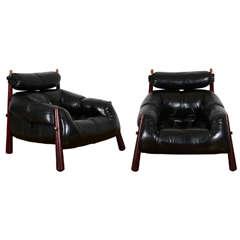 Percival Lafer - Paire de fauteuils  1958  Bois de Jacaranda garnis de cuir noir en partie capitonné. Pieds fuselés à montage apparent.  85 x 95 x 92 cm  Percival Lafer est un designer brésilien qui est spécialisé en sièges, très souvent recouverts de cuir, et qui a aussi dessiné quelques tables basses.Il a suivi des études d'architecte à Sao Paulo puis reprit la compagnie de meubles de son père. Cette activité lui prenait beaucoup de temps, mais il a construit des maisons modernistes pour quelques amis. Il a aussi la passion de la conception de voitures.Son leitmotiv c'est l'innovation, la création qui doit refléter les technologies modernes, et les tendances contemporaines pour la Société de consommation. Il est pour un Design différent, original, mais patenté.
